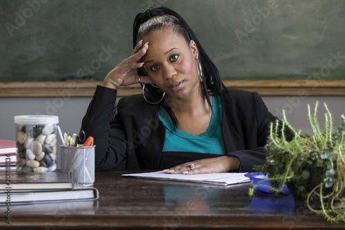 Valokuva  Overwhelmed black female teacher sitting at her desk