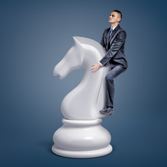 A tiny businessman rides a large white chess knight piece on a blue background.