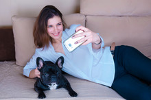 Young Girl Taking Selfie With Dog. Black Active French Bulldog Lay On The Couch. Happy, Smiling Dog Lover, Dogman  Hug,hold Pet. Cute Caucasian Teenager In Modern, White Shirt. Woman Looking To Phone