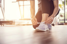 Woman Tying Running Shoes On Black Floor Background In Gym With Sunlight. Copy Space.