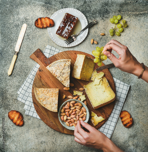 Fotografie, Obraz Flat-lay of cheese platter with cheese assortment, green grapes, bread, honey and nuts with female hands reaching to food over grey concrete background, top view
