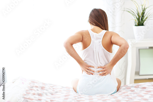 Young woman waking up in bed with backache Wallpaper Mural