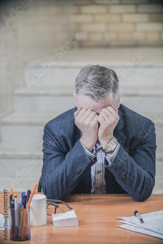 Fototapeta distressed sad businessman sitting in despair in the office obraz