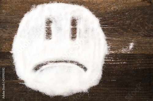 Fototapeta Face of a sad smiley made with granulated sugar. The picture illustrates the harm of eating sugar and salt, as well as dependence on flavoring additives. obraz