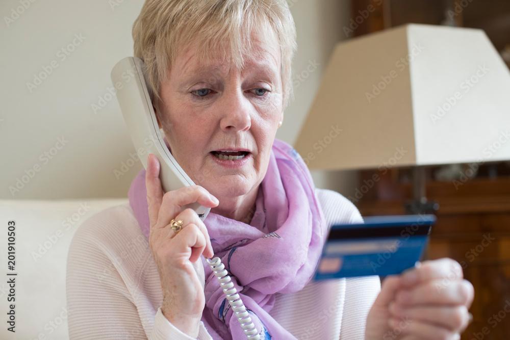 Fototapeta Senior Woman Giving Credit Card Details On The Phone
