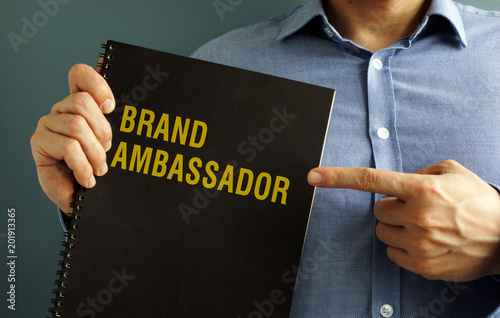 Man is holding book with title Brand Ambassador. Wallpaper Mural