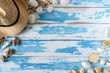 Seashells on blue wooden board with straw hat. Summer holiday background.