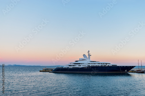 Big luxury super motor yacht at dock of the port on background of sunset.