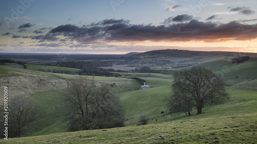 Poster Khaki Stunning vibrant sunrise landscape image over English countryside landscape with lovely light hitting the hills