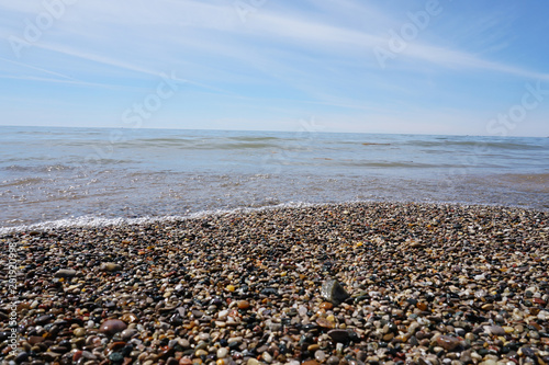 Foto op Aluminium Grijze traf. Water washing on shoreline over pebbles on beach on bright sunny day