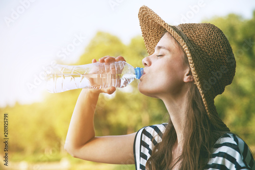 Woman drinking water in summer sunlight