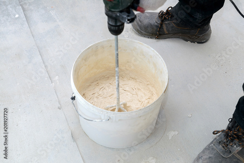 Fotografie, Obraz  Mixing of a plaster by an electric drill in plastic bucket