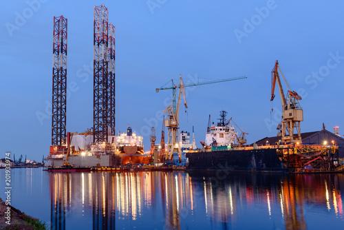 Fotografia, Obraz Oil rig docked in shipyard of Gdansk at dusk. Poland