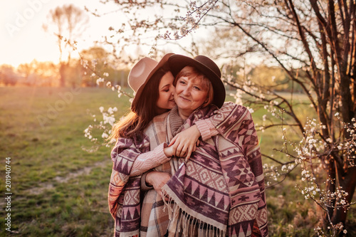 Middle-aged mother and her adult daughter hugging in blooming garden. Mother's day concept. Family values