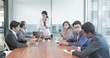 A ambitious and attractive female boss is interacting with young management team of mixed gender and ethnicity in modern office building. A motivated woman conducting a board meeting with executives.