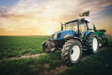 a tractor with a sack of fertilizer moves along the field in the spring