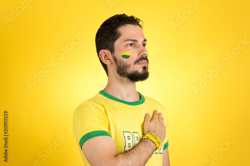 Brazilian supporter of National Team of football is listening to National anthem with hand on the chest Wallpaper Mural