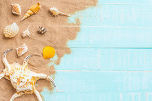 Beach Accessories Including Sunglasses, Hat Beach, Shell And Sand On Bright Blue Pastel Wooden Background For Summer Holiday And Vacation Concept.