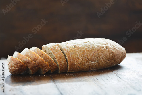 Fotografie, Obraz  Sliced loaf fresh bread wooden table view straight