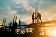 canvas print picture - Silhouette of engineer and construction team working at site over blurred background sunset pastel for industry background with Light fair.