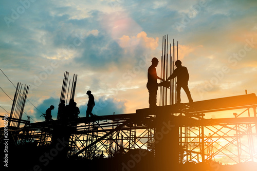 Fotomural  Silhouette of engineer and construction team working at site over blurred background sunset pastel for industry background with Light fair