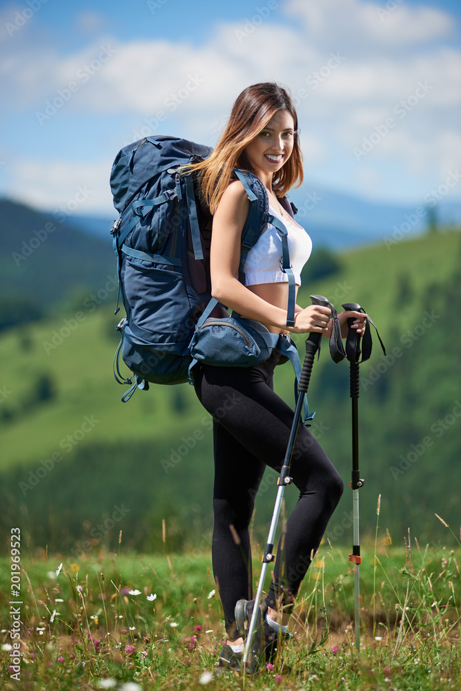 Fototapety, obrazy: Full-length portrait of beautiful sporty girl hiker with blue backpack and trekking poles posing on the top of a hill, smiling to the camera in the mountains. Concept of active lifestyle