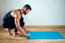 The Man's Hand Spreads The Yoga Mat On The Floor. Blue Yoga Mat