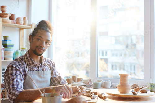Foto  Portrait of handsome confident mixed race man in apron looking at camera while m