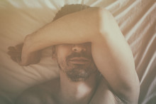 Depressed Man Lying In His Bed And Feeling Bad. Soft Focus.