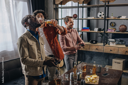 Bar side view of multiethnic male friends drinking beer while playing with joysticks together