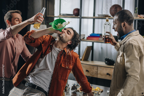 Bar drunk male friends drinking alcohol beverages from funnel at party