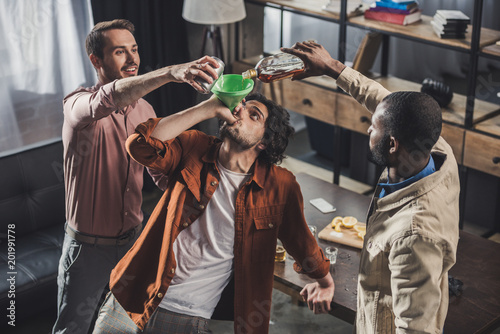 Bar high angle view of man drinking from funnel while friends pouring alcohol beverages from glass bottle and can