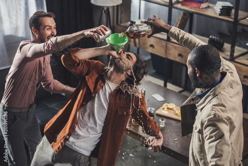 Foto auf AluDibond Bar high angle view of man drinking from funnel while friends pouring alcohol beverages