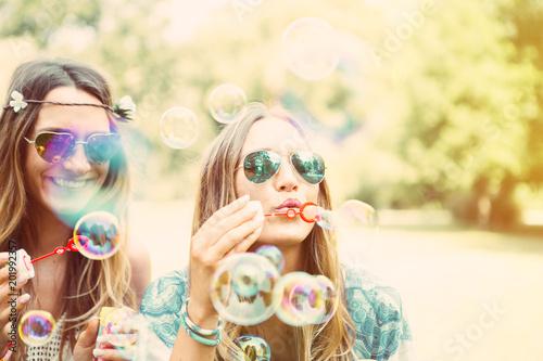 Fotografija  freundinnen machen seifenblasen in einem park. zwillinge