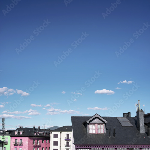 Minimal urban picture of some candy-colored buildings' rooftops from a little village. Day scene with a wide clear and blue sky with some clouds.