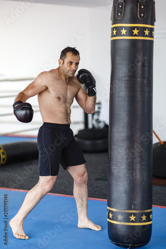 Photo  Kickbox fighter training in a gym with punch bags, see the whole series