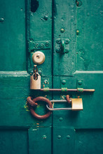 Old Green Door Behind Many Locks. Behind Seven. Lock And Key Concept.