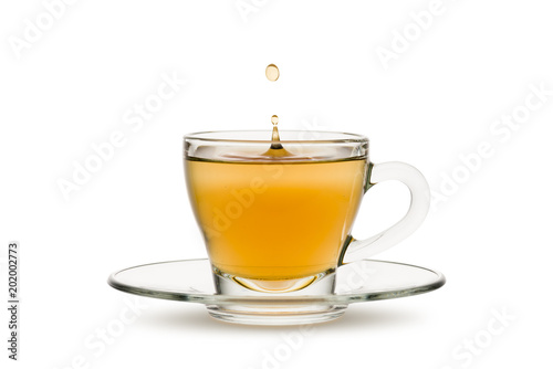 tea in glass cup with drop splashing, on white background.