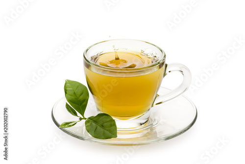 Photo  tea in glass cup with leaves and drop splashing, on white background