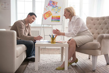 Art And Psychotherapy. Focused Man Visiting Jovial Psychologist While Trying Art Therapy