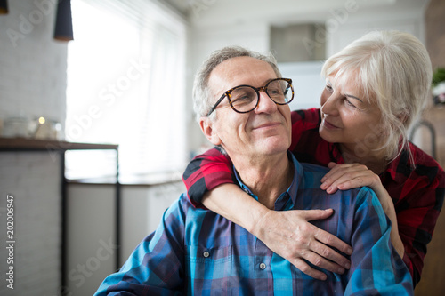 Fotomural  Happy senior woman embracing her husband
