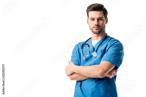 Cuadros en Lienzo Surgeon  wearing blue uniform with stethoscope standing with folded arms isolate