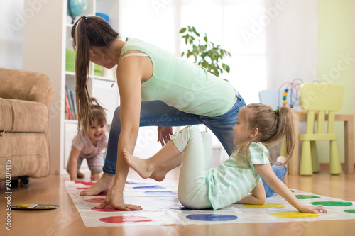 Fotografia, Obraz Young mother playing twister with her children daughters
