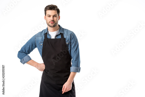 Fotografia portrait of young bearded waiter in apron standing akimbo isolated on white