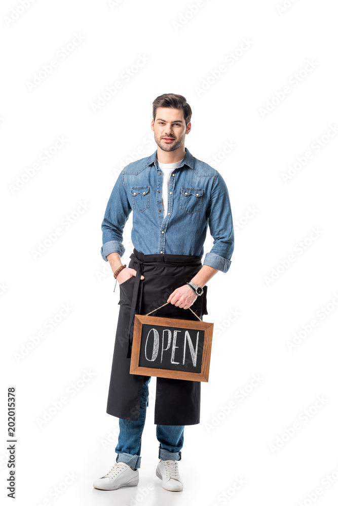 Fototapeta young waiter in apron with open blackboard isolated on white