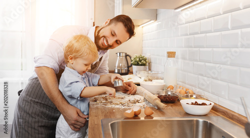 Poster Cuisine happy family in kitchen. father and child baking cookies