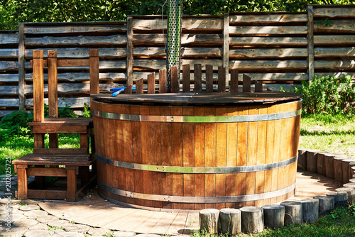 Leinwand Poster Modern wooden hot tub with stairs in garden outdoor, copy space