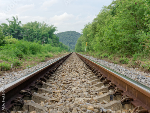 Keuken foto achterwand Spoorlijn Old vintage metal railway track or line with stone on the ground, trees on the side, heading to mountain with business concept of journey, voyage, trip, aim, reach, achievement, and success