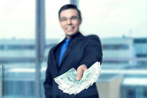 Fototapeta Twoje finanse - mężczyzna wręcza gotówkę, pożyczkę, chwilówkę obraz