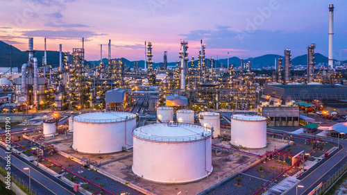 Fototapeta Aerial view oil and gas chemical tank with oil refinery plant background at twilight, business power and energy chemical barrel. obraz